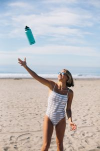 girl in the beach tossing waterbottle