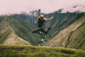 woman jumping with a nice mountain